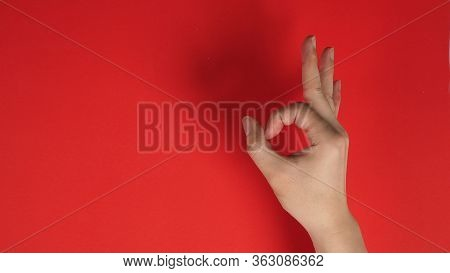 The A-ok Hand Sign With Right Hand On Red Background.