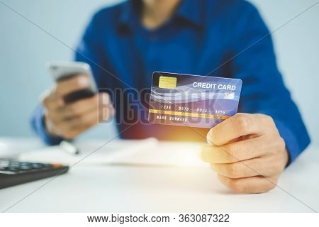 Businessman In Blue Shirt Entering Security Code With Mobile Phone And Paying With Mock Up Credit Ca