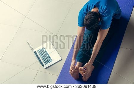 Man Stretching At Home Before Or After Exercising. Fitness Training, Stretching, Exercises Online. S