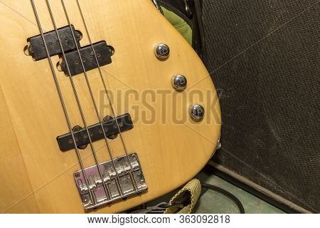 The Lower Part Of The Body Of A Four-string Bass Guitar With Strings, Pickups And Volume And Tone Co