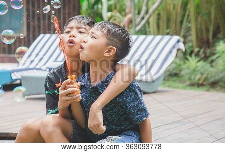 Cute Boys Are Blowing A Soap Bubbles Outside. Indonesian Or Malasian Brother Siblings Are Playing To