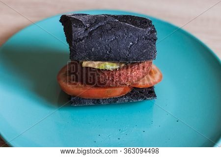 Side View A Beyond Delicious Plant Based Non Meat Burger With Avocado, Tomato And Charcoal Bread.