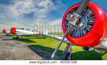 Historical Aircrafts On An Airfield Against A Cloudy Sky