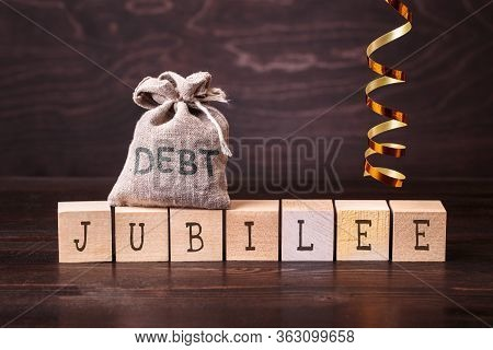 Debt Jubilee Spelled In Letters On Bag And Wooden Blocks Against Dark Background. The Concept Of Deb