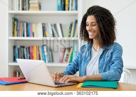 Laughing Latin Female Student Learning Language Online At Computer At Home
