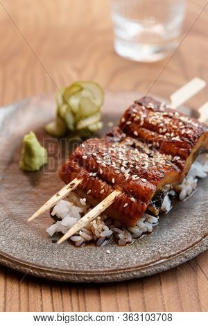 Fried unagi eel with barbecue sauce and rice in clay plate
