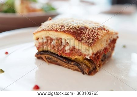 Piece of moussaka, traditional Greek dish, on white plate