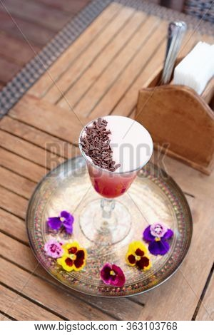 Red cocktail with froth and chocolate shaving on restaurant table