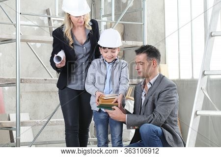 Couple Of Architect And Construction Engineer Together With Their Son Choose The Samples To Plan The