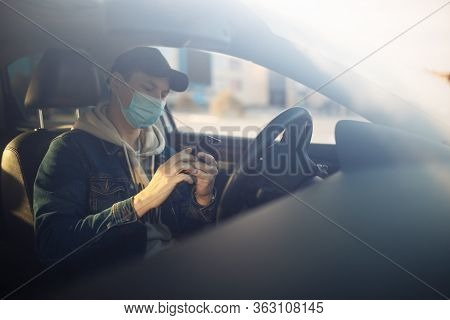 A Man Wearing A Medical Mask Holds A Mobile Cell Phone In His Hand While Driving A Car. Boy Driver C