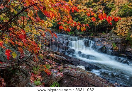 Unique Waterfall Framed By Red Leaves