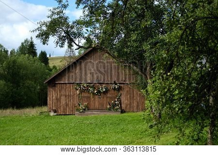 Old Barn Brown Wall Wood Background Surrounded By Green Trees. The Barn Is Decorated With Flowers An