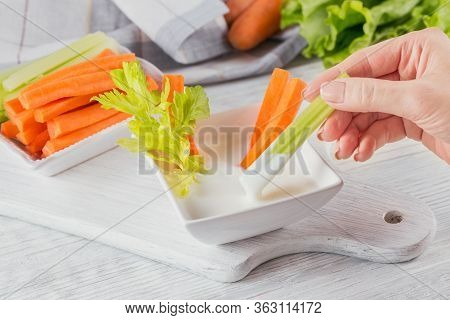 Vegetable Sticks. Fresh Celery And Carrot With Yogurt Sauce. Womans Hand Holding Celery Stick. Healt