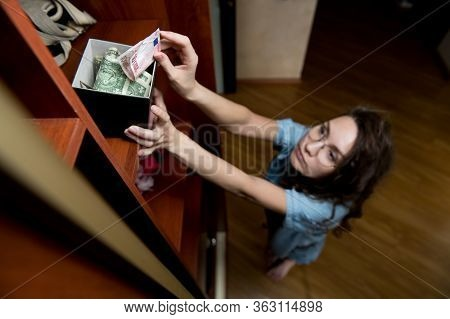 A Girl Puts Or Takes Dollars From A Money-box On The Top Shelf Of A Closet. Selective Focus On The P