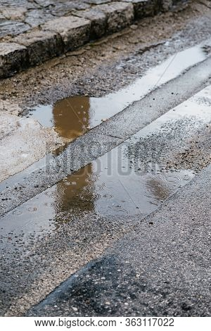 Raindrops In A Puddle On The Pavement. Circles On The Water From A Drop Of Rain In A Puddle On The A