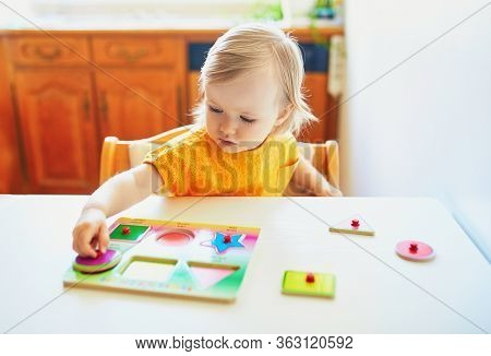 Adorable Toddler Girl Doing Wooden Puzzle. Child Learning Geometric Shapes. Kid Learning To Solve Pr