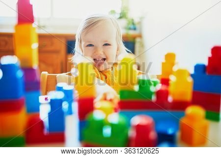 Adorable Little Girl Playing With Colorful Plastic Construction Blocks At Home, In Kindergaten Or Pr