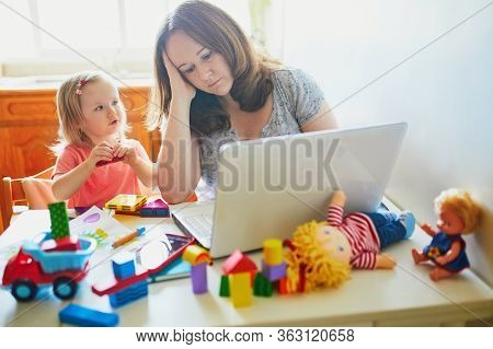 Exhausted And Stressed Mother Working From Home With Toddler. Quarantine And Closed Daycare Centres