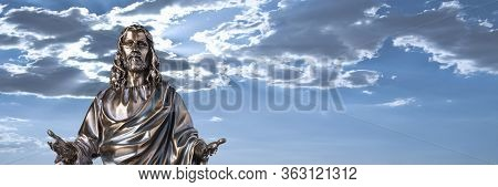 A Bronze Statue Of A Jesus Christ With A Dramatic Sky