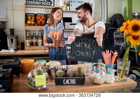 young couple opening their own cafe, making announcement with a sign on a board