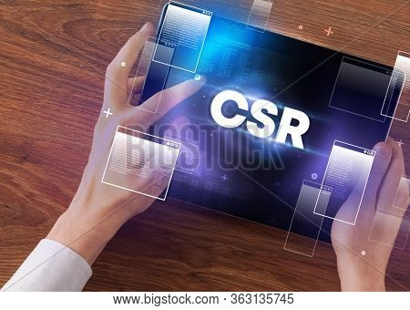 Close-up of a hand holding tablet with CSR abbreviation, modern technology concept