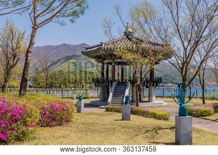 Jinan, South Korea; April 21, 2020: Oriental Pavilion Behind Tree And Series Of Iron Welded Sculptur