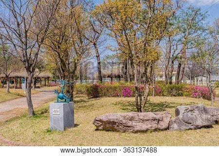 Jinan, South Korea; April 21, 2020: Sculpture Of Welded Metal In Public Park Beside Two Large Boulde