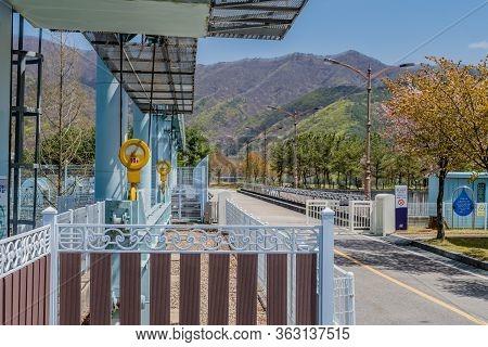 Jinan, South Korea; April 21, 2020: Yongdam Dam Hoist Gate Deck And Paved Road Across Spillway.