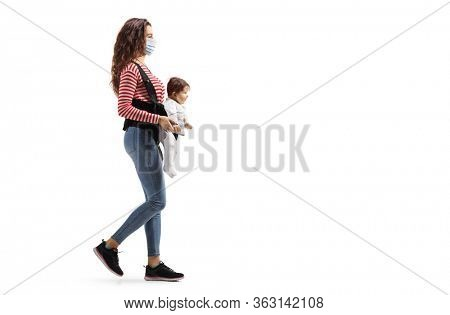 Full length profile shot of a mother with a baby in a carrier wearing a protective medical mask and walking isolated on white background