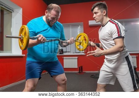 A Fat Man In The Gym Performs Barbell Lifting Exercises At The Limit Of His Powers Under The Guidanc