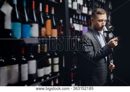 Sommelier Man Holds Glass With Red Wine In Restaurant, Tests Aroma And Color