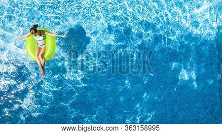 Active Young Girl In Swimming Pool Aerial Top View From Above, Child Relaxes And Swims On Inflatable