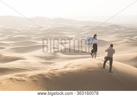 A Husband Photographs His Wife In The Desert. A Married Couple Is Photographed On Journey Through Th