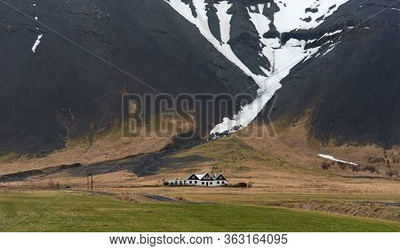 Typical Icelandic  Landscape At  With Farmhouses Under The Mountain Covered In Snow In Iceland. Sout
