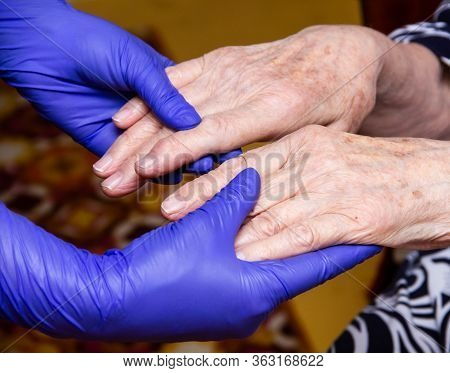 Old Man's Hands Support Hands In Medical Gloves