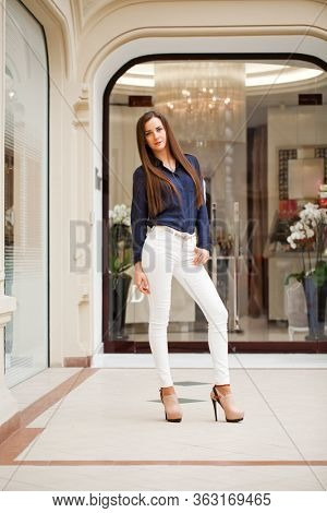 Young beautiful brunette woman in white pants and blue shirt in the mall