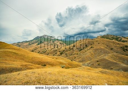 Beautiful Scenic Landscape Hills With Dry Yellow Grass Under Dramatic Cumulonimbus Clouds In Summer