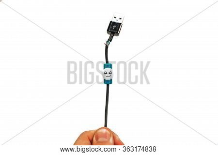 Hand Holding A Black Torn Usb Cable On A White Background