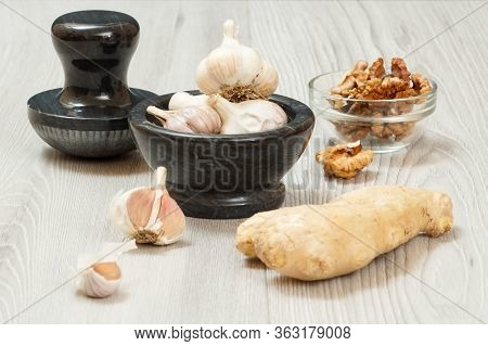 Health Remedy Relief Foods For Cold And Flu With Ginger, Garlic And Walnuts On Wood Boards. Foods Th