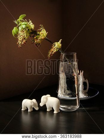 Still Life With Flowering Spring Twig Of Ash-tree With Young Leaves In A Glass Vase, Two Small Toy E