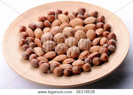 walnuts almonds and hazelnuts in a round dish