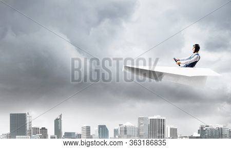 Businessman In Aviator Hat And Goggles Driving Paper Plane In Storm. Crisis Management Concept. Side
