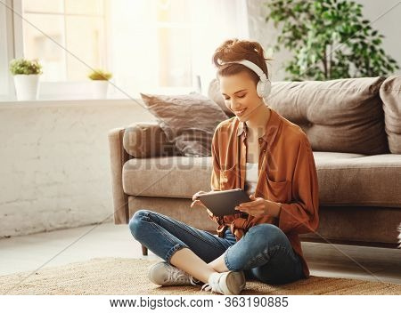 Young Satisfied Female In Casual Clothes And Wireless Headphones Surfing Digital Tablet While Sittin