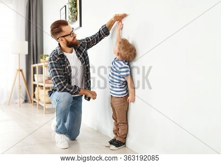 Concept Of Development, Growing Up. A Father Measures Height Of His Young Child Son