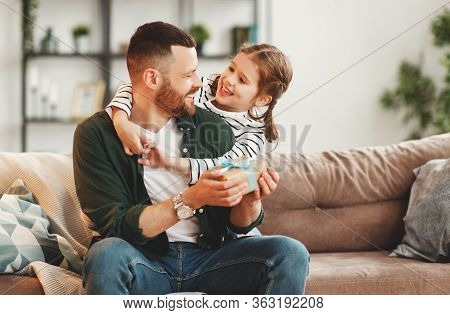 Happy Young Man With Gift In Hand And Adorable Little Daughter Embracing And   Looking At Each Other