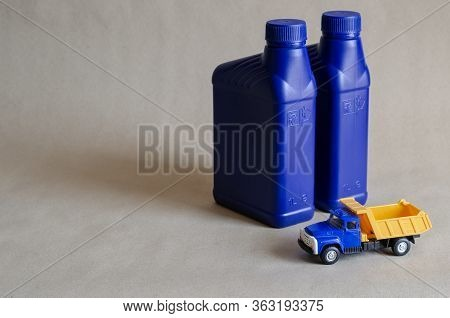Two Plastic Canisters With Car Oils And A Toy Dump Truck. Plastic Containers For Automotive Lubrican