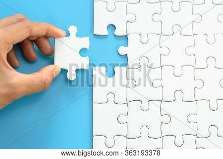 White Jigsaw In The Hands, The Correct Solution. Teamwork, Solving And Completing The Task. Last Pie