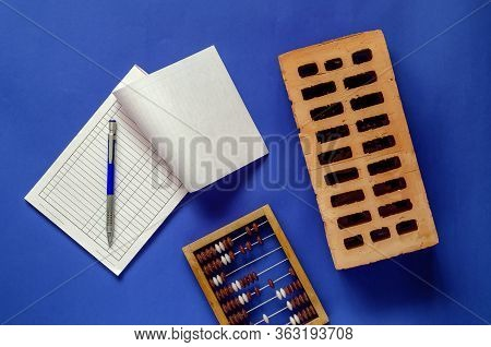 Brick, Blank Invoice And Wooden Abacus On A Blue Background. New Red Brick, Blank Invoice Form With