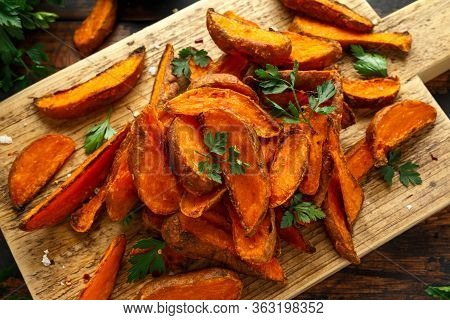 Healthy Baked Orange Sweet Potato Wedges With Dip Sauce, Herbs, Salt And Pepper On Wooden Board