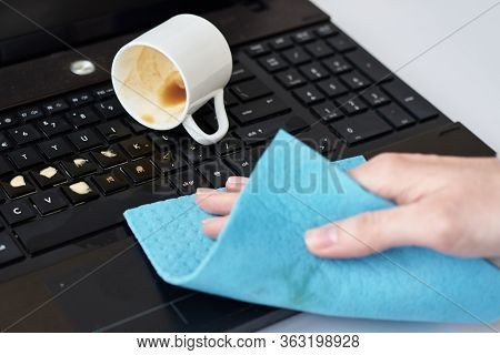 Hand Cleans Spilled Coffee On Laptop Keyboard With A Rag